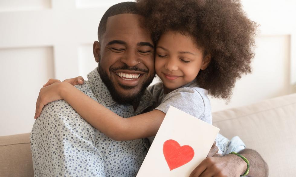 Ein Vater hat seine Tochter auf dem Schoß und sie umarmen sich, während er eine Karte mit einem Herz hält.