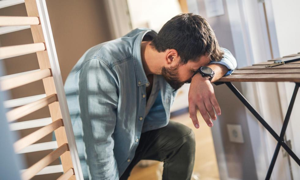 verzweifelter-Mann-mit-unfertigen-Möbeln