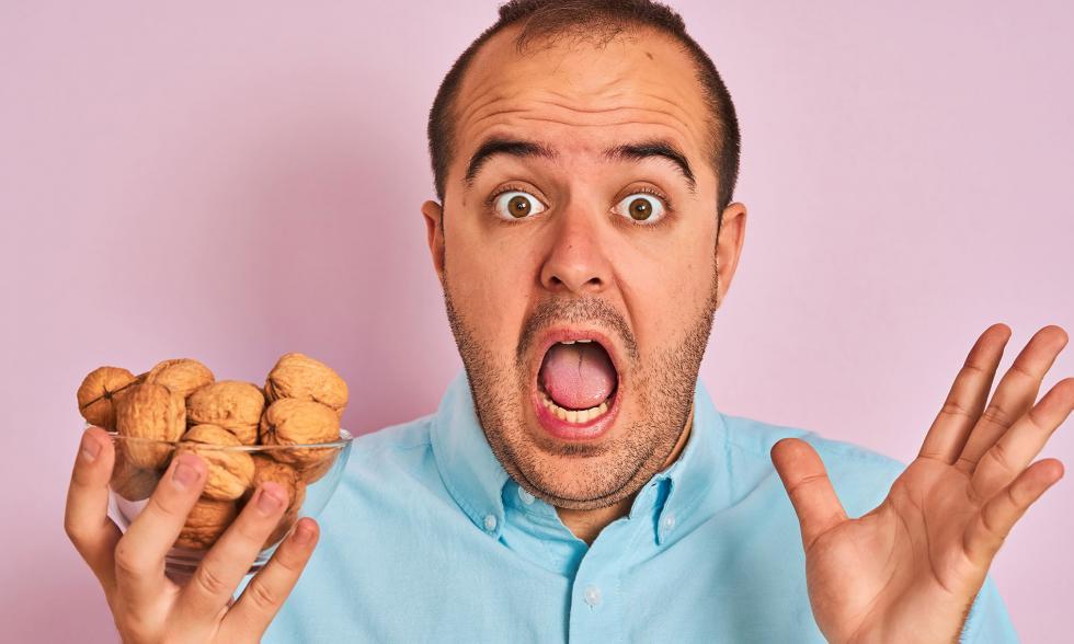 Mann mit einer Schalte Nüsse