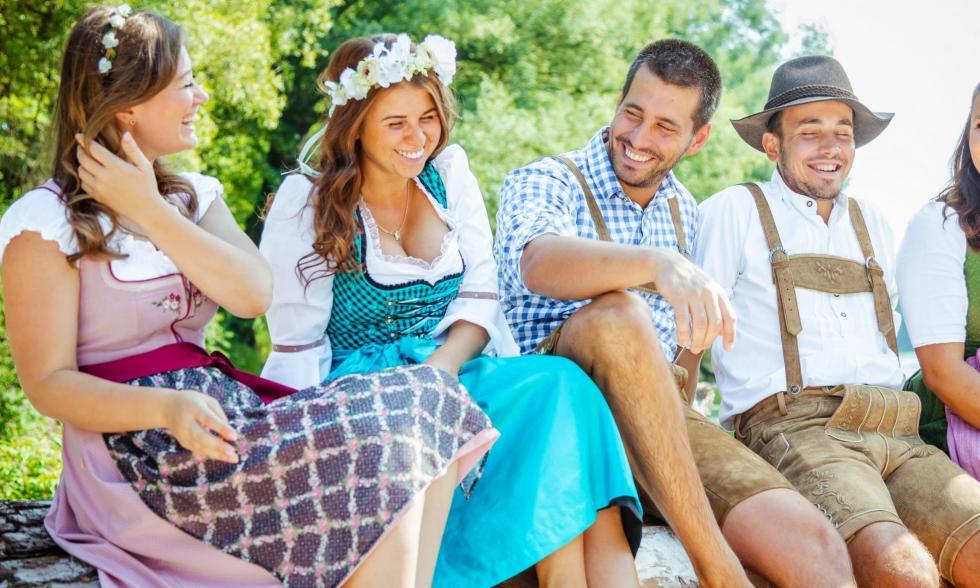 Damen und Herren sitzen auf einem Baumstamm in Trachten