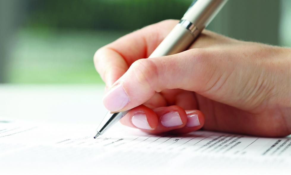 Rechtschreibung im Deutschen - Hand mit Stift