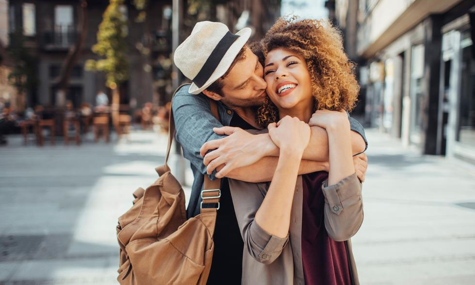 Sich umarmendes Paar in einer Fußgängerzone