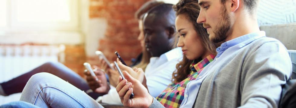 People sitting on a couch and looking on their smartphones using the Offline dictionary  advanced app of PONS