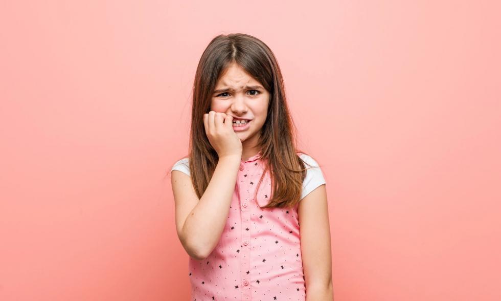 Mädchen vor pfirsichfarbenen Hintergrund kaut auf ihren Fingernägeln