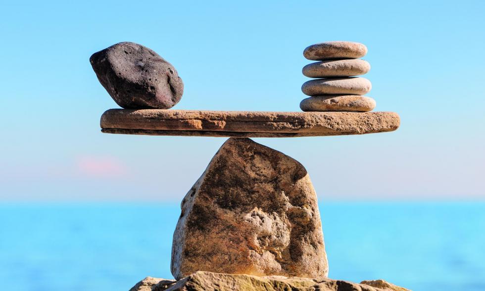 Ein Stein am Strand mit einer Spitze balanciert einen flachen Stein auf sich, der wiederum jeweils links und rechts weitere Steine auf sich balanciert.