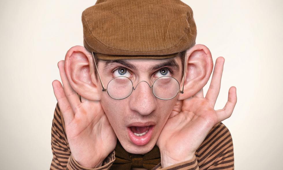 Junger Mann mit braunem Hut und braun gestreiftem Pullover klappt seine Ohren auf