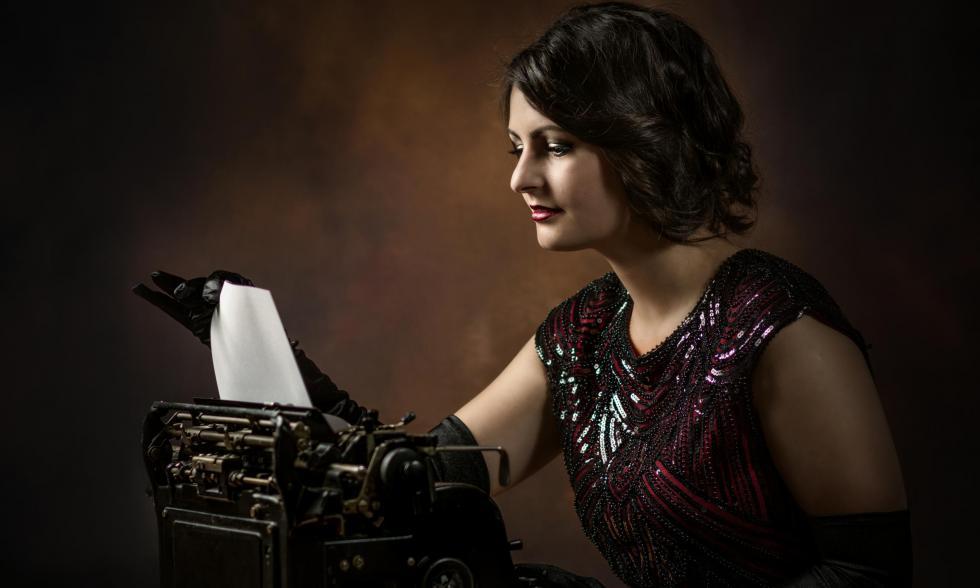 schick gekleidete Frau vor einer Schreibmaschine